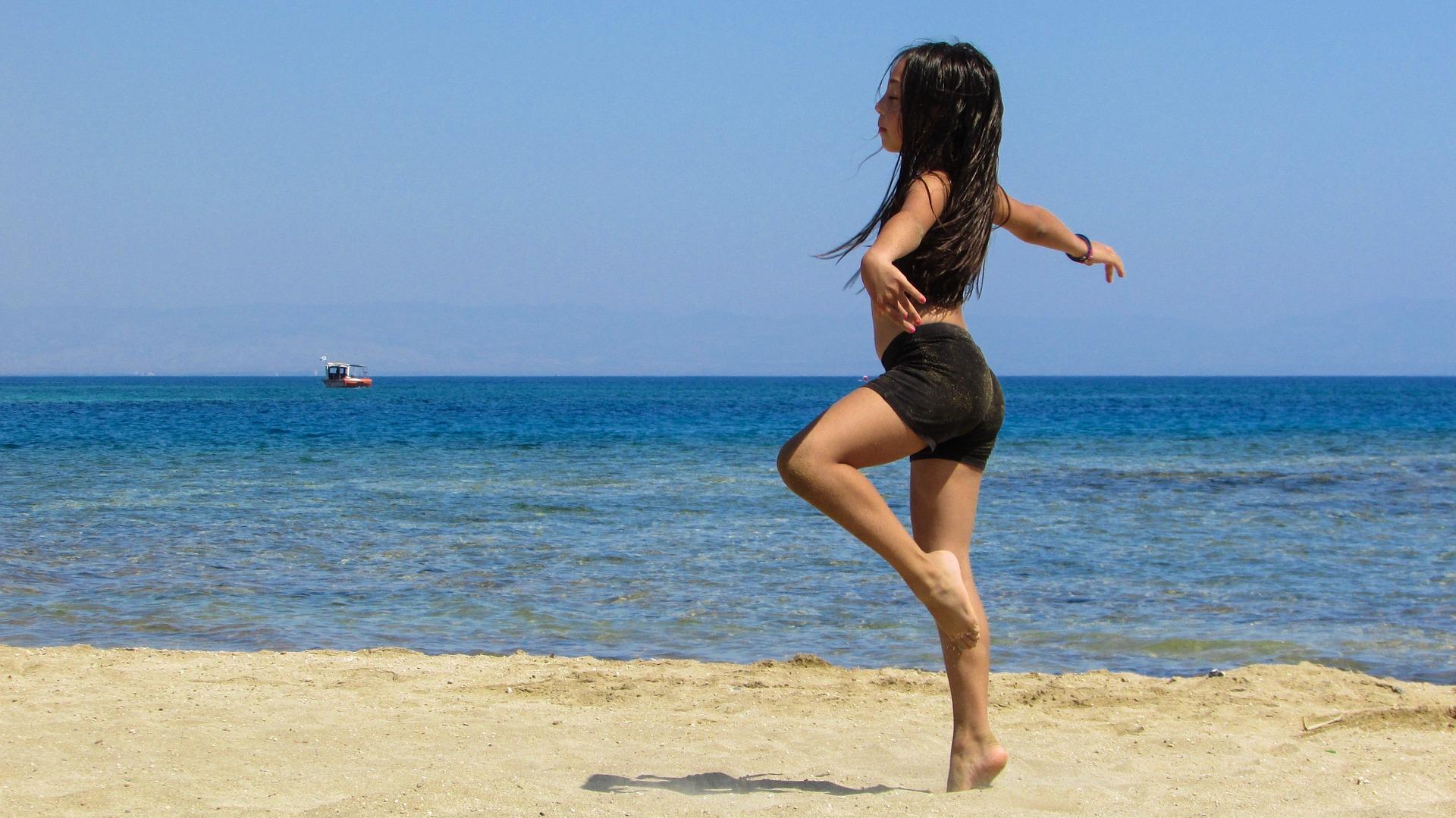girl dancing on the beach by ocean