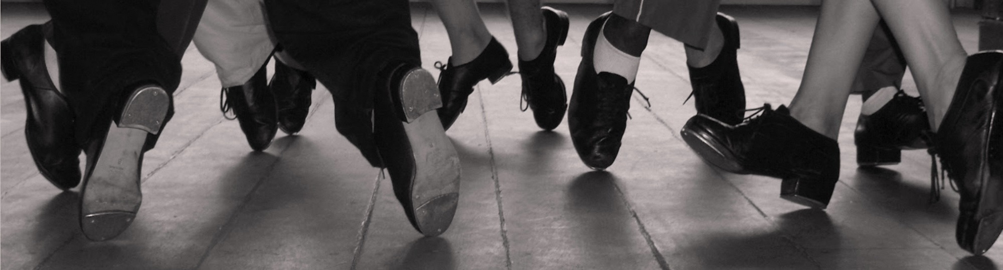 Tap dancers in the middle of routine, photo is a view of only their tap shoes