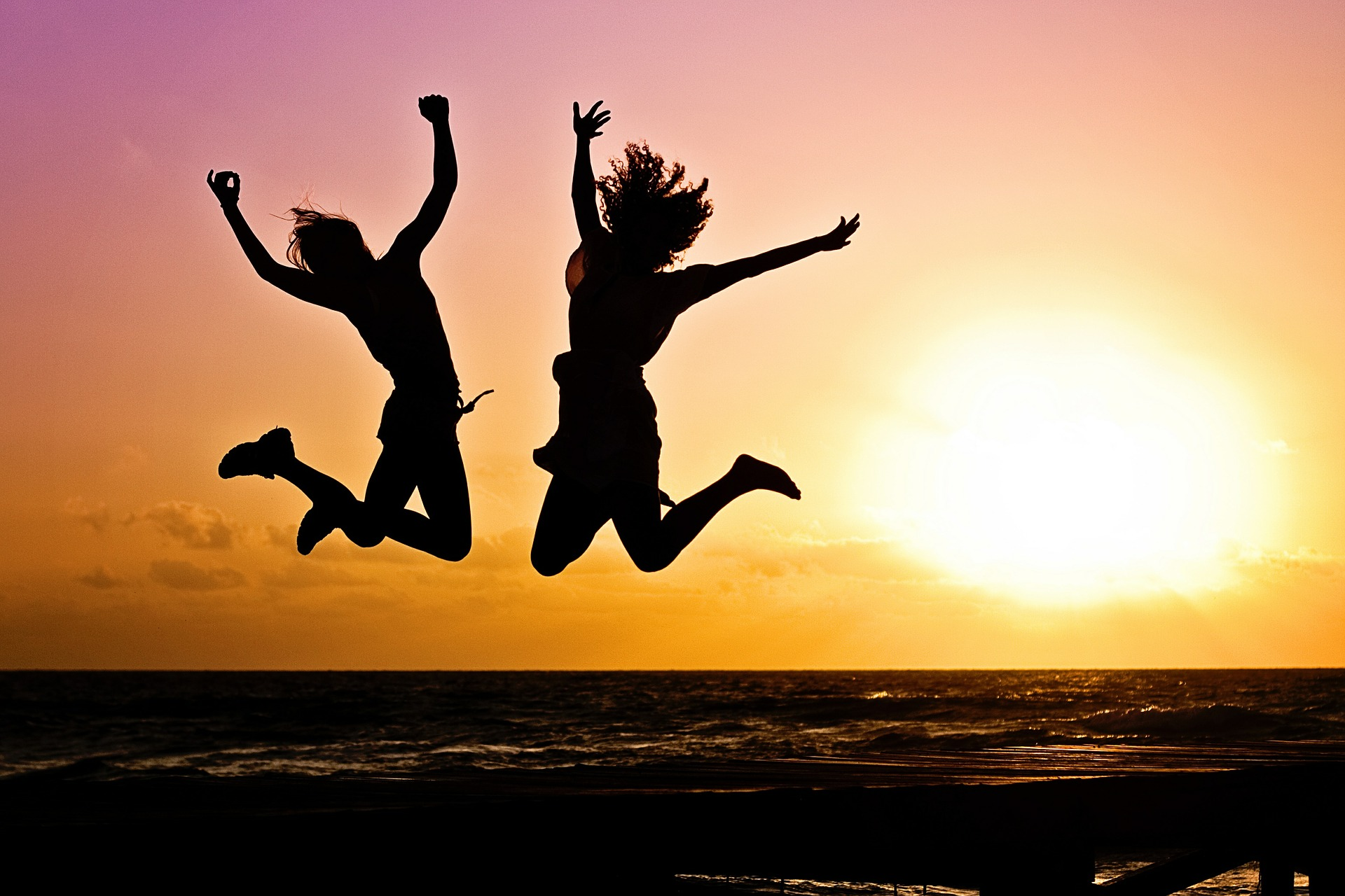 two girls jumping in celebration on the beach